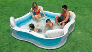 Familie hat Spaß in einem aufgeblasenen Pool. Er ist quadratisch und hat eine Sitzmöglichkeit in jeder Ecke