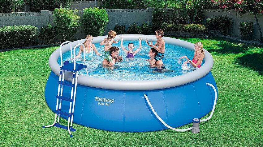 großer Pool mit genügend Platz für mehrere erwachsene Menschen drinnen. Im Hintergrund stehen grüne Büsche und eine weiß Mauer ist zu sehen.