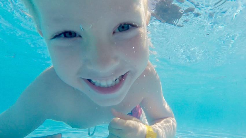 Kind, dass unter Wasser taucht und in eine Kamera lächelt.