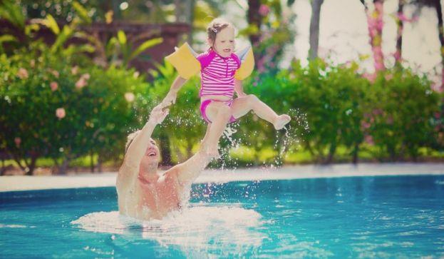 Vater wirft sein Kind hoch. Gleich wird es aus gut einem Meter im Pool landen. Es lacht.
